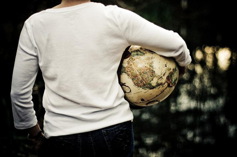 Mujer de espaldas sosteniendo un globo del mundo